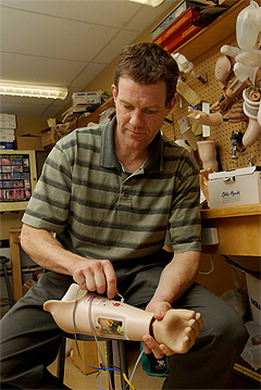 Dr. Kevin Englehart works on a prosthetic arm. His team's research will help give future prosthetics the ability to feel.